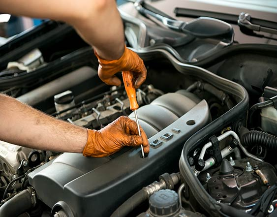 person standing over a car engine using a screwdriver to repair