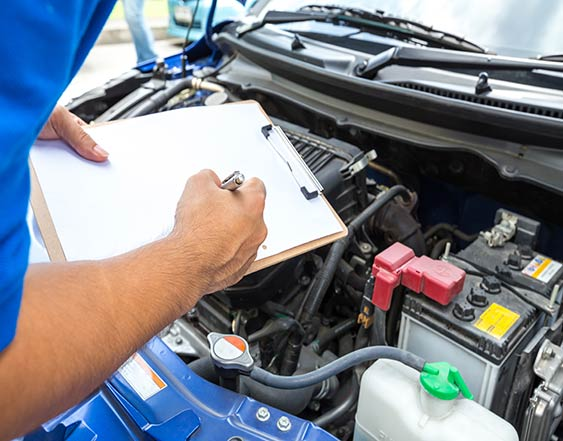 person standing by car with bonnet open taking notes on a checklist