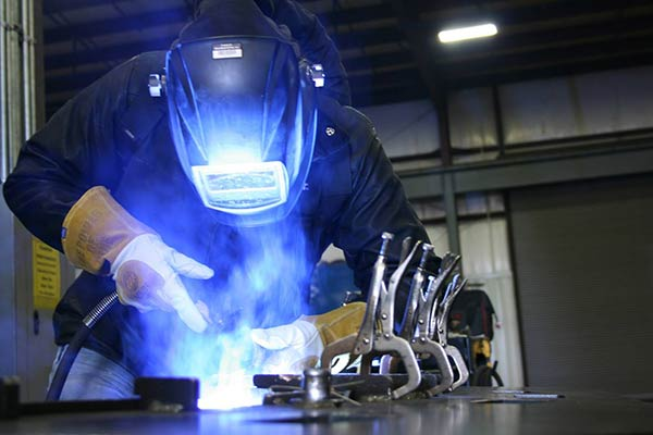 Person wearing protective helmet and gloves whilst welding on a work surface